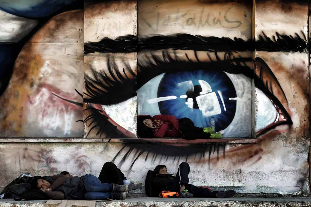 Migrants sleep in front of graffiti illustrating an eye at the port of Mytilene on the Greek island of Lesbos, on October 6, 2015. Europe is grappling with its biggest migration challenge since World War II, with the main surge coming from civil war-torn Syria. AFP PHOTO / ARIS MESSINIS